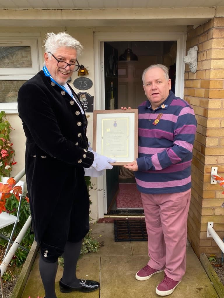 The High Sheriff, in ceremonial dress presents a framed certificate to Cllr Poluton on the doorstep of his home