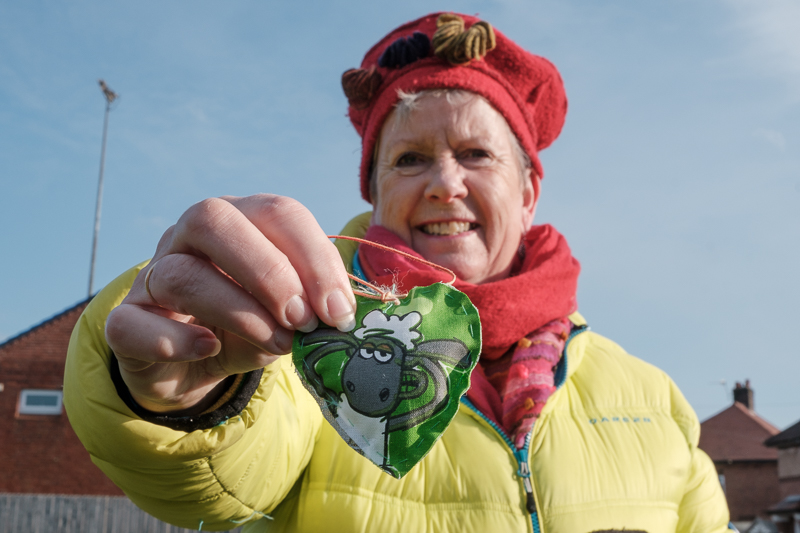 Photo of one of the WI members holding a green fabric hear with a picture of a cartoon sheep