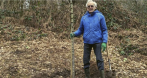 Photo of Tom in a blue jacket, holding a spade alongside the tree sapling