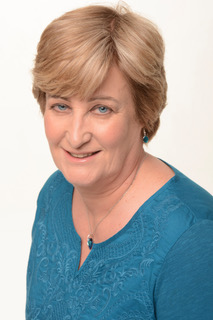 Portrait photo of Chester Cathedral Poet in Residence Julia McGuinness wearing a blue top.